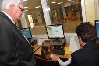 Rogers and Shriver watch student take an AR test